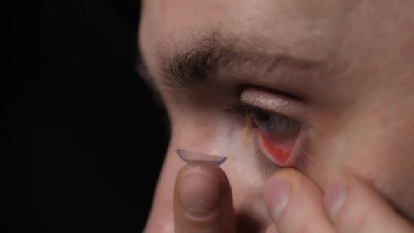 Thumbnail for Young Handsome Man Putting Contact Lens in His Blue Eye  Isolated on Black Background.