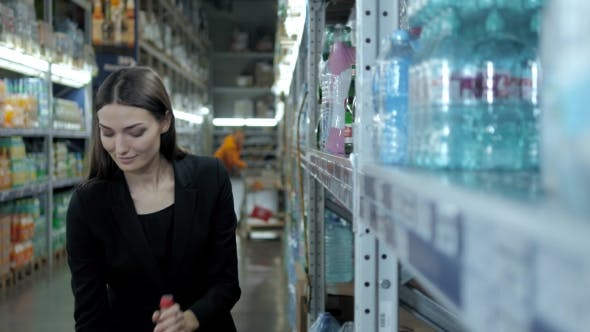 Thumbnail for Smiling Woman Buying a Bottle of Water