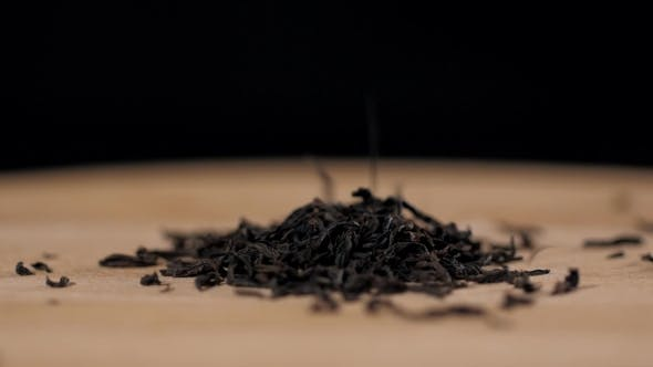Thumbnail for Black Dry Tea Leaves Isolated on Black Background Pouring Down