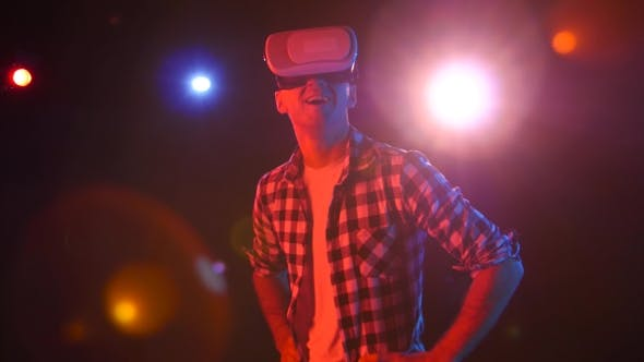 Thumbnail for Man with Delight Watching in Virtual Reality Glasses. Red Spotlights