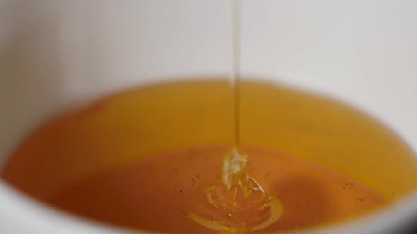 Thumbnail for Thin Honey Trickle Against a Black Background