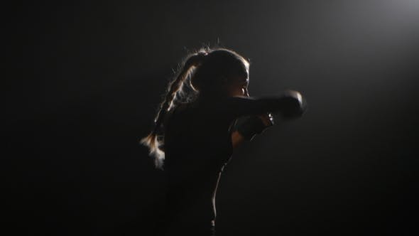 Thumbnail for Girl Sends a Boxer Hitting Opponent. Silhouette. Black Background . Side View.