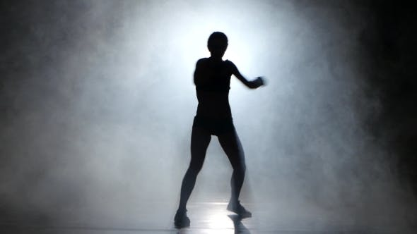 Thumbnail for Girl Kickboxer Gloves Sends the Punches. Silhouette. Black Background. Lights Rear