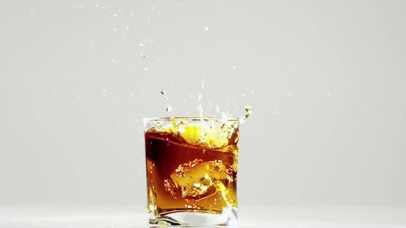Zwei Eiswürfel fallen in Glas mit Bourbon.