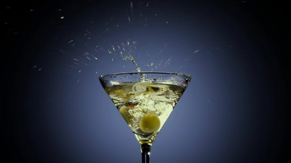 Thumbnail for Two Olives Fall Into Tall Martini Glass. Black Background