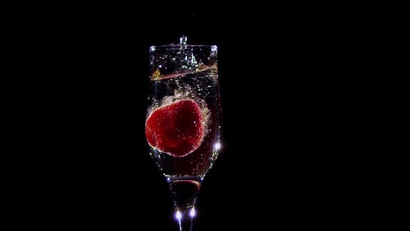 Thumbnail for . Fresh Strawberry Falling in Glass with Champagne Wine