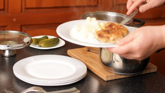 Woman Lays Down Meal On Plates