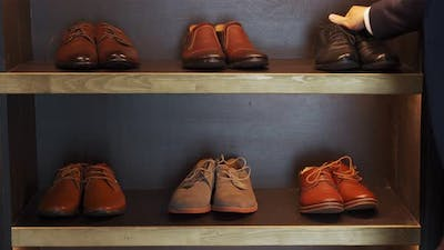 A Man Chooses Shoes to Buy in a Shoe Store