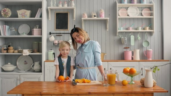 Thumbnail for Beautiful Happy Mother with Orange Juice Child Boy in Kitchen Smiling, American Family Morning