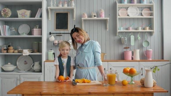 Thumbnail for Schöne glückliche Mutter mit Orangensaft Kind Junge in der Küche lächelnd, American Family Morning
