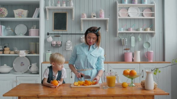Thumbnail for Healthy People - Little Boy and Young Mom Mother - Making Fresh Orange Juice in the Kitchen at
