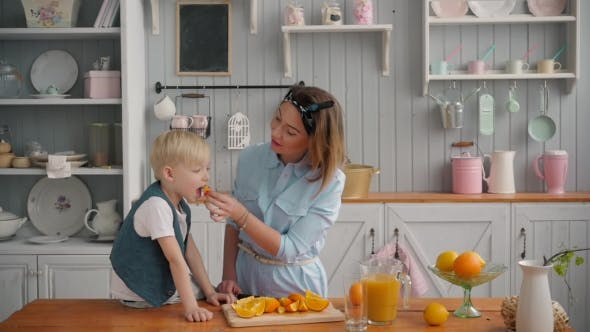 Thumbnail for Happy Mother and Little Son Child Boy in the Kitchen, Happy Time and Togetherness, Mom Holding Fresh