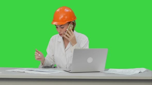 Thumbnail for Woman in Orange Hardhat Calling the Phone Discussing Constraction Plan on a Green Screen, Chroma Key