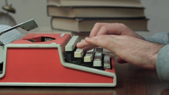 Thumbnail for Man's Hands Typing on a Red Typewriter