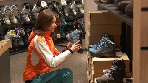 Woman Looks at Sports Shoes in a Store