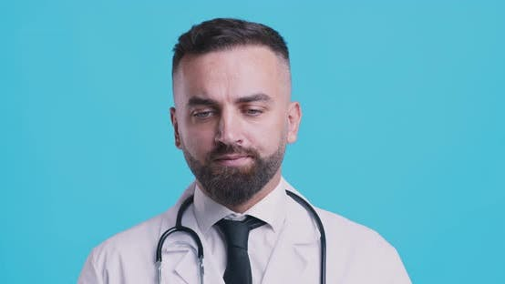 Thumbnail for Serious Medical Doctor Shaking Head No After Contemplating, Blue Studio Background