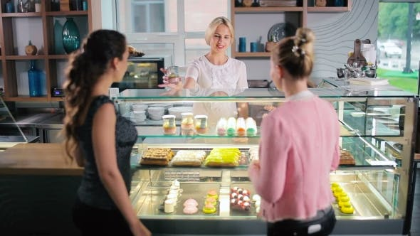 Cover Image for Women Stand Near the Windows with Desserts