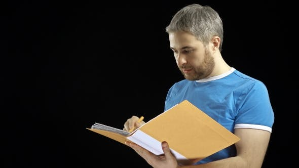 Thumbnail for Handsome Man in Blue Tshirt Looking Through Papers in Yellow Folder