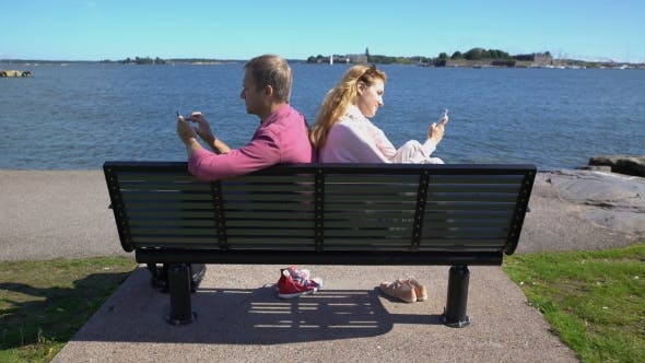 Thumbnail for A Couple Sitting on a Bench on the Beach and Using Their Smartphones