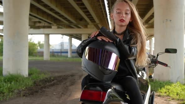 Biker Girl with Moto Helmet Sitting on Motorcycle Under Car Bridge in City, Moto Girl in Black