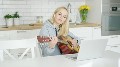 Female Guitarist Practicing at Home