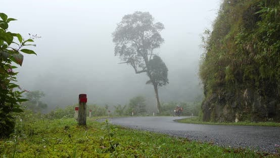 Thumbnail for Couple on a Motorbike Traveling on a Paved Curvy Road in the Misty Mountains.