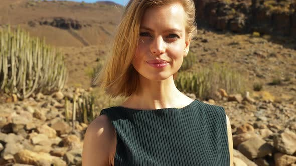 Thumbnail for Model Whipping Hair Back on a Sunny Day with Cactus and Rocks in Background