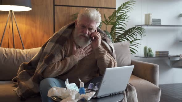 Thumbnail for A Sick Elderly Person Calls the Doctor on the Phone. A Man Is Ill and Is Sitting on the Couch at