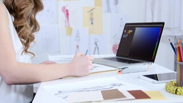 Thumbnail for Künstler schaut sich den Computer an und wählt Farbtöne für eine neue Sammlung von Kleidung