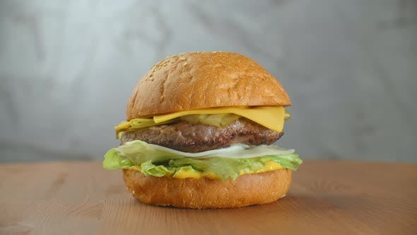 Thumbnail for A Delicious Cheeseburger Served on a Wooden Platter
