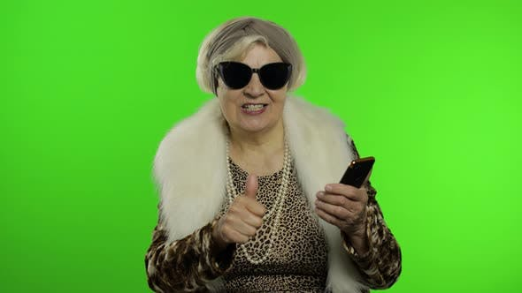 Thumbnail for Caucasian Grandmother Woman Using Smartphone, Pointing at Camera with Hand