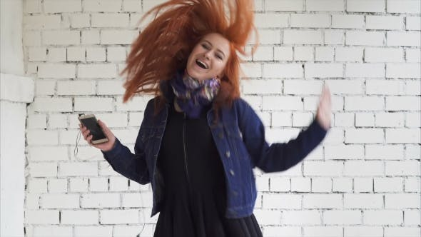 Thumbnail for Happy Young Ginger Woman Dancing with Smartphone