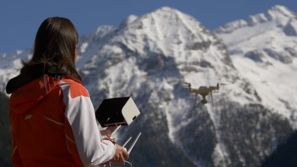 Woman with a Remote Control Controls the Drone