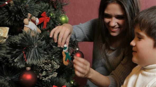 Thumbnail for Mother with Son Hang the Decorating Teddy Bear on Christmas Tree