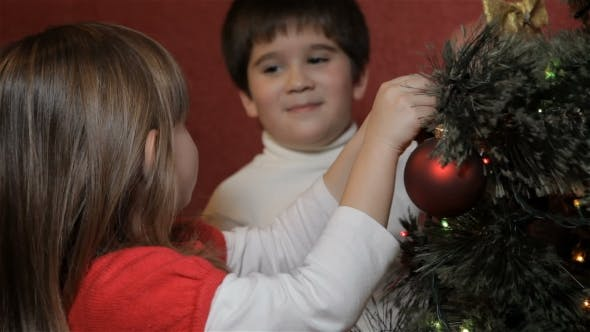 Thumbnail for Little Boy Hangs Decorating Bow on Christmas Tree