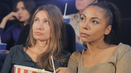 Two Women Looking at the Screen at the Movie Theater