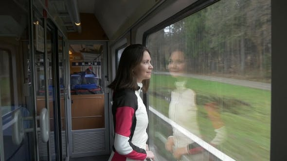 Thumbnail for Woman Looks Out the Window in a Train and Smiles