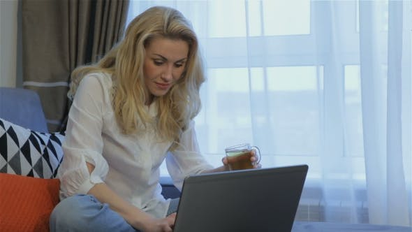 Thumbnail for Woman Drinks Tea Near the Laptop at Home