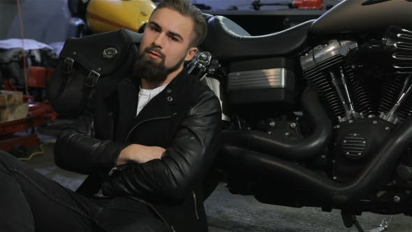 Thumbnail for Male Biker Sits on the Floor Near the Motorcycle