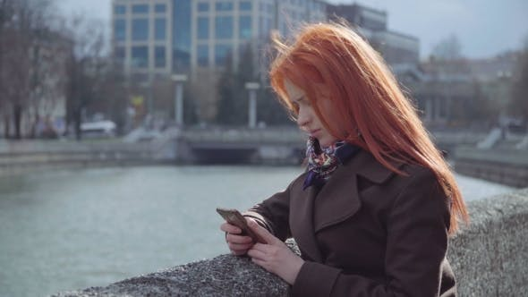 Thumbnail for Young Sad Lonely Ginger Woman Using Smartphone Outdoors