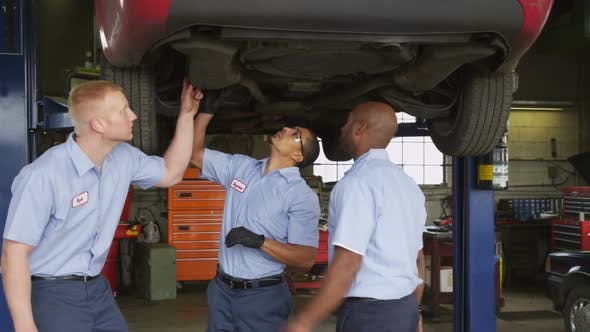 Thumbnail for Three auto mechanics look at car together