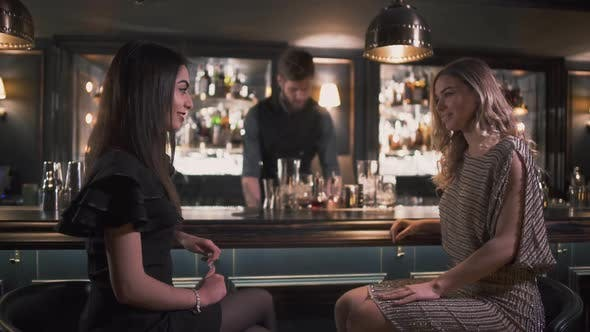 Thumbnail for Bartender Serving Cocktails To Pretty Girls While the Are Chatting and Smiling at the Modern Bar