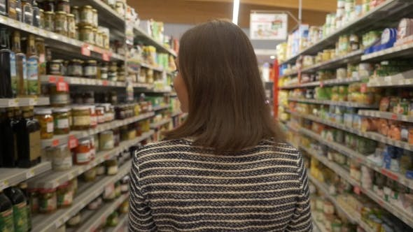 Thumbnail for Woman Walking Along Shelves with Products