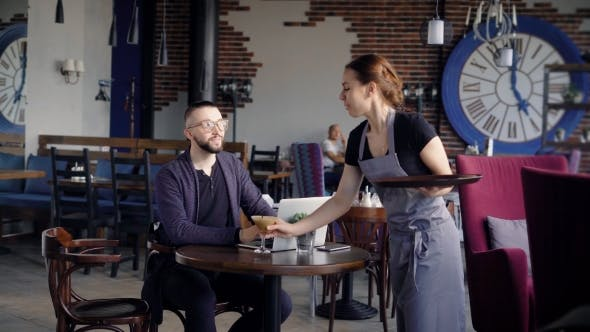 Thumbnail for The Waitress Brings a Cup of Coffee or Cappuccino To Businessman. on the Table Laptop and Cell Phone