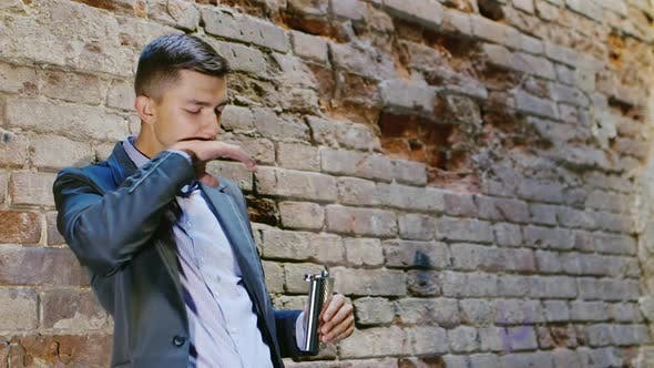 Thumbnail for Young Frustrated Businessman Drinking Alcohol From Flasks. In an Abandoned House. Concept