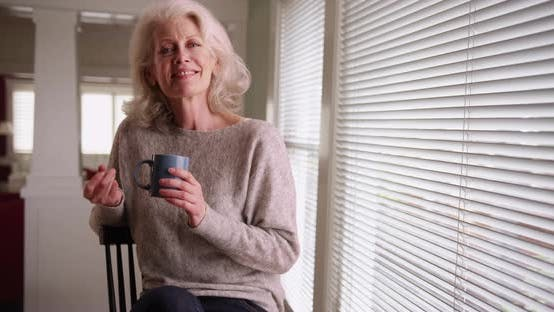 Thumbnail for Cheerful elder woman holding coffee mug snapping her fingers smiling at camera