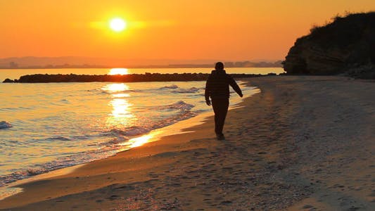 Thumbnail for Man Walks On The Beach At Sunset