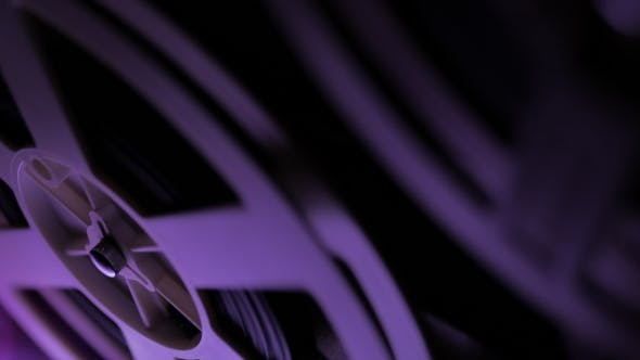 Thumbnail for Old 8Mm Film Projector Playing in the Dark Room with Violet Light.  of a Reel with a Film.