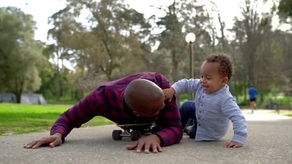 Mixed-race Little Boy and Father Playing with Scateboard
