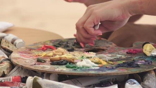 Artist Painter Extrudes on Palette Oil Paints of Different Colors